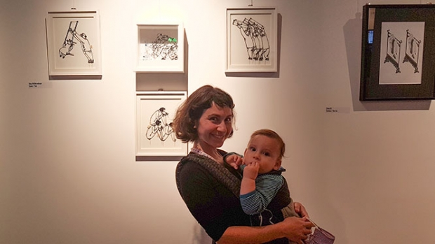 Dina Velikovskaya, holding her son, with panels from her film Ties