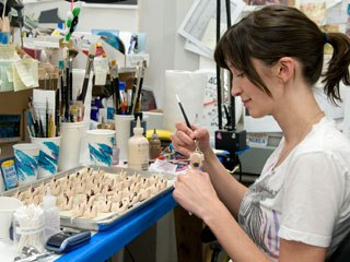 Character painter Angela Kiely paints the replacement faces for the character of Other Mother. Each puppet has two heads, each with a different expression. Photo Credit: Galvin Collins.