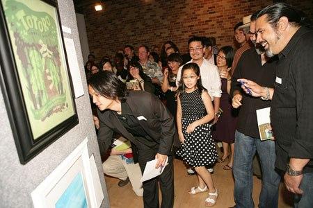 Dice Tsutsumi bids on an art piece. (Photo by Deborah Coleman / Pixar)