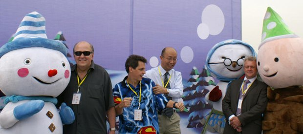 Mark Simon dancing on stage in China, surrounded by Snowmen characters, Bill Dennis on camera left and Joe Guo to the right of Mark.