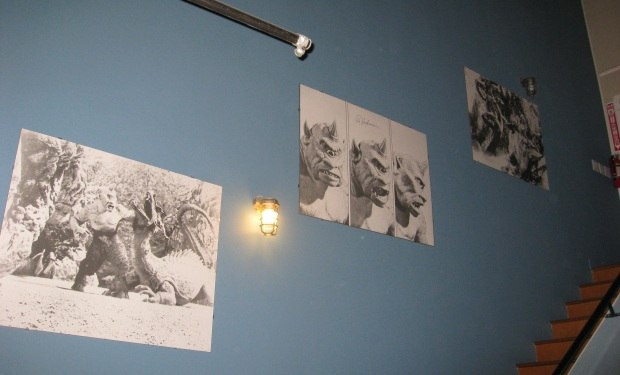 A series of signed Ray Harryhausen film scene prints adorn an office wall.