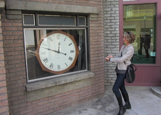 Wendy adjusts her watch to the clock shop prop.