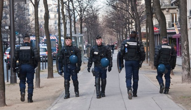 French riot police waited on alert outside the Paris apartment where the pilot was shot this past February.
