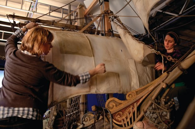 Manon Wright, Assistant Art Director, and Laura Savage, Set Dresser, tie on and adjust the Pirate Ship's sails.