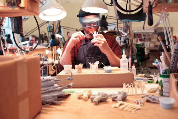 Aaron Matthews carefully paints details on a hand.