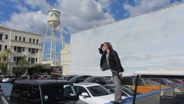 David's photo op beside the skyline backdrop and the parking lot / floodable water tank.