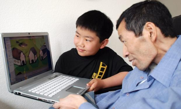 """Perry Chen showing his dad Dr. Changyou Chen animation scene from """"Changyou's Journey"""" July 14, 2012 (photo by Brian Bostrom)"""