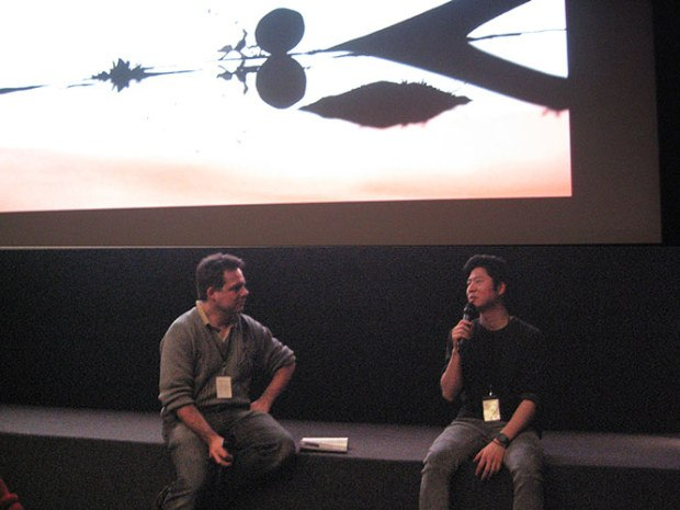 Olivier Catherine interviewing Erick Oh under image from one of Erick's film.