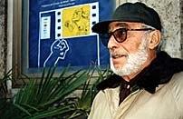 Osvaldo Cavandoli next to the Cartoombria '97 festival poster which he designed. Photo courtesy of Chiara Magri.
