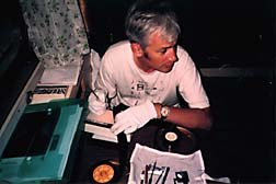 Paul Bush demonstrating his scratch-on-film technique in a makeshift studio in his cabin. Photo © oTTo Alder.