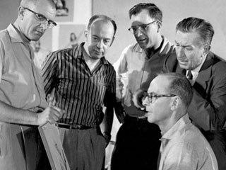 (Left to right) Milt Kahl, Marc Davis, Frank Thomas and Ollie Johnston (seated) with Walt Disney. © Disney.